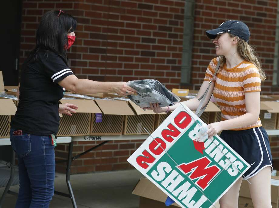 Kyleigh McKim is handed her graduation robes as seniors at The Woodlands High School picked up graduation appeal and yard signs, Friday, May 8, 2020, in The Woodlands. Photo: Jason Fochtman/Staff Photographer / 2020 ? Houston Chronicle