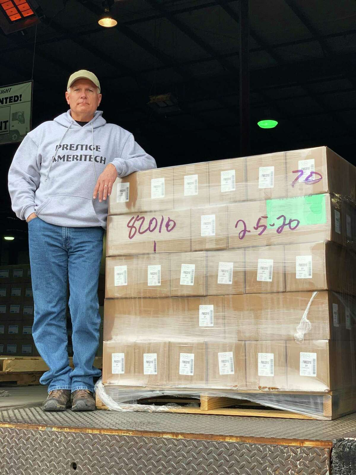 Mike Bowen, Vice President of Prestige Ameritech, stands with a truck load of masks to be sent to MD Anderson Cancer Center.