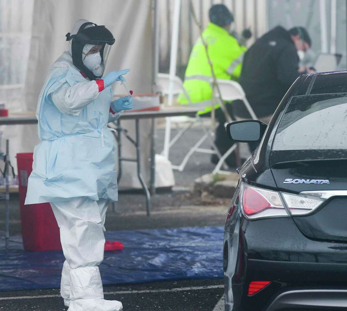 Medical personnel from Murphy Medical Associates administer drive-thru screenings for the COVID-19 coronavirus at a mobile testing site set up at Cummings Beach in Stamford, Conn. , March 20, 2020.