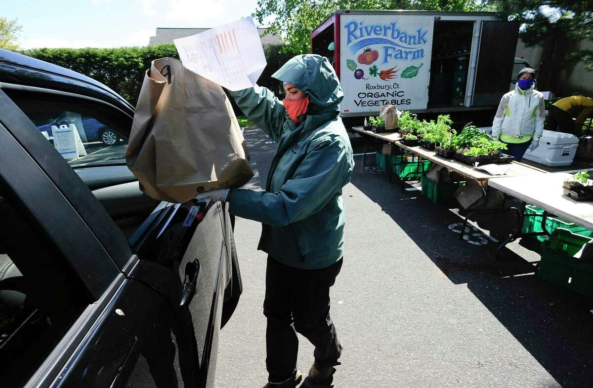 Mackenzie Brandt of Riverbank Farm in Roxbury, Connecticut, places hands off a bag of fresh produce to a customer as she drove up to the stand at the New Canaan Farmers Market re-opened recently in the Center School parking lot. The traditional open air market made some significant changes this year, in response to the coronavirus pandemic. Market customers were required to place their orders online with the various vendors and were given a time slot to arrive at the market to pick up orders. Each vendor set up an online payment system for each customer, then a system pre-packaged orders that would be delivered using a curbside pick-up system. Site staff, as well as vendors placed individual orders into the customers' cars, thus limiting contact and exposure from the virus. Market organizers set up 20 minute time slots, estimating 20 cars per each slot, with the 300 allotted slots from customers who went online signing up for a slot. The slots were taken in a matter of days upon posting of the new procedures for the market. The market continued on Saturday, May 16. It began at 10 a.m., and went until 3 p.m. It was a walkable one with safe social distancing starting Saturday, May 30. It will continue to do so with the protocol every Saturday.