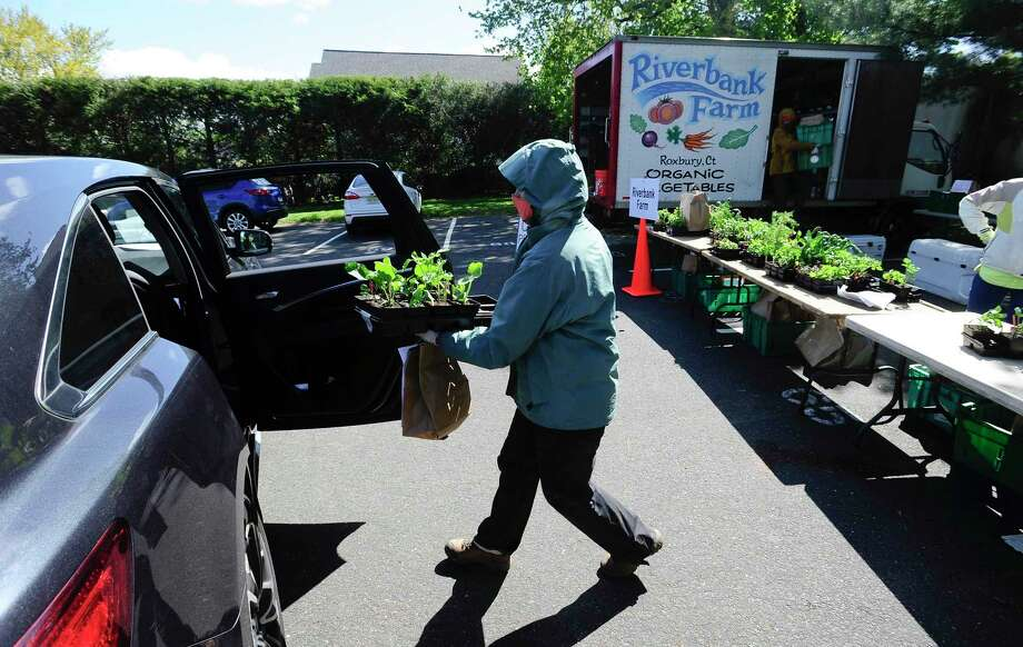Mackenzie Brandt of Riverbank Farm in Roxbury, Connecticut, places a flat of various fresh herbs and flowers into a customers car at the New Canaan Farmers' Market re-opened recently in the Center School parking lot. The traditional open air market made some significant changes this year, in response to the coronavirus pandemic. Market customers were required to place their orders online with the various vendors and were given a time slot to arrive at the market to pick up orders. Each vendor set up an online payment system for each customer, then a system pre-packaged orders that would be delivered using a curbside pick-up system. Site staff, as well as vendors placed individual orders into the customers' cars, thus limiting contact and exposure from the virus. Market organizers set up 20 minute time slots, estimating 20 cars per each slot, with the 300 allotted slots from customers who went online signing up for a slot. The slots were taken in a matter of days upon posting of the new procedures for the market. The market continued on Saturday, May 16. It began at 10 a.m., and went until 3 p.m. Photo: Matthew Brown / Hearst Connecticut Media / Stamford Advocate