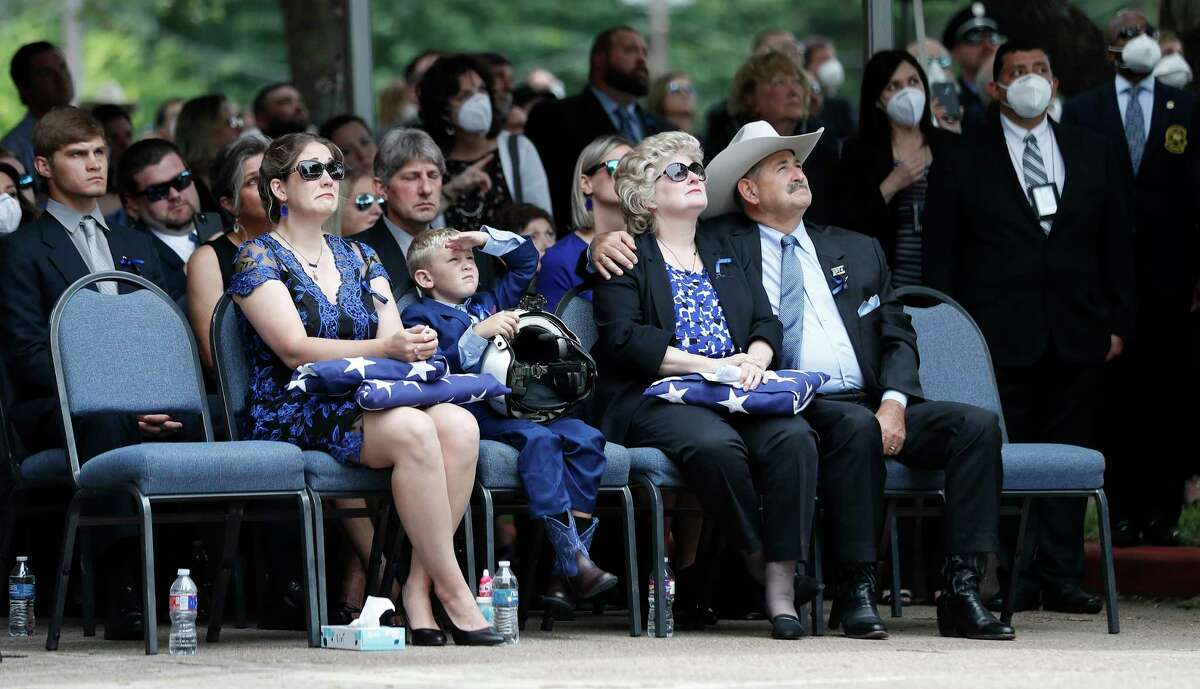 Keira Knox, wife of Houston Tactical Flight Officer Jason Knox, and her son, Cooper holding his dad's flight helmet and his parents, retired officer and Houston City Councilman, Mike Knox and his wife, Helen look up at the flyover and missing man formation of the HPD Air & Marine Division during his funeral at Houston's First Baptist Church, in Houston, Saturday, May 9, 2020.