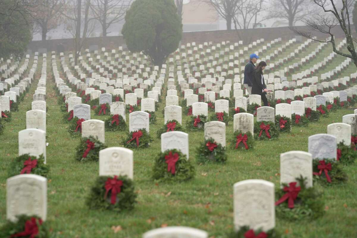 FILE - In this Dec. 14, 2019, file photo, people walk among headstones with holiday wreaths in Arlington National Cemetery during Wreaths Across America Day in Arlington, Va. Coronavirus has more people addressing their end-of-life planning. And for those who haven't, ita€™s a great time to take it on. (AP Photo/Sait Serkan Gurbuz, File)
