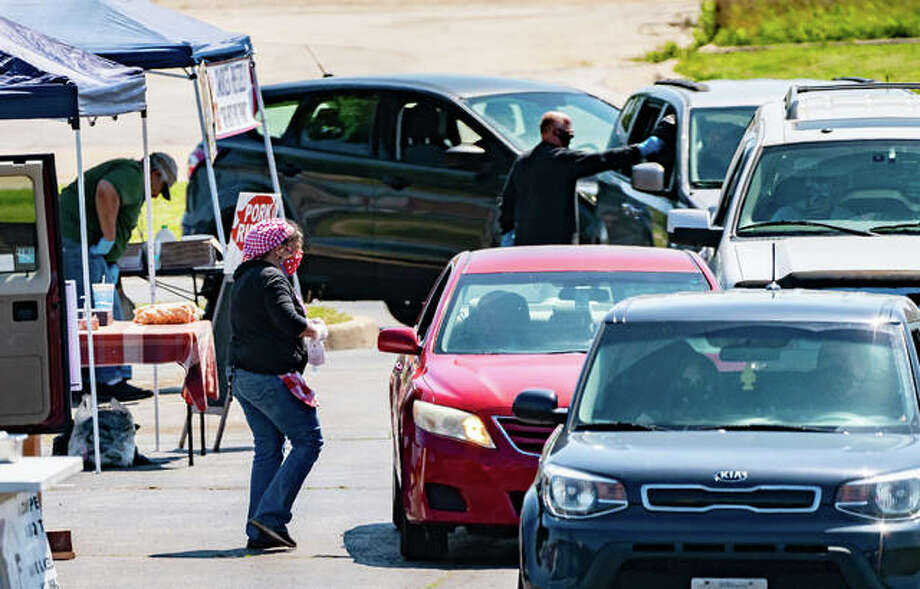 Kathleen McKeever, owner of Frost Bakery, approaches a customer's vehicle Saturday during the opening of a drive-through version of the Alton Farmers' & Artisans' Market. Photo: Nathan Woodside | The Telegraph