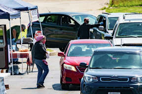 Kathleen McKeever, owner of Frost Bakery, approaches a customer's vehicle Saturday during the opening of a drive-through version of the Alton Farmers' & Artisans' Market.