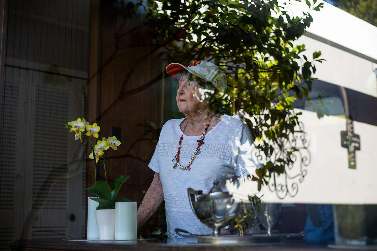 Corinne Mullane, 94, checks on her blossoms outside her yard on April 24, 2020 in San Mateo, CA.