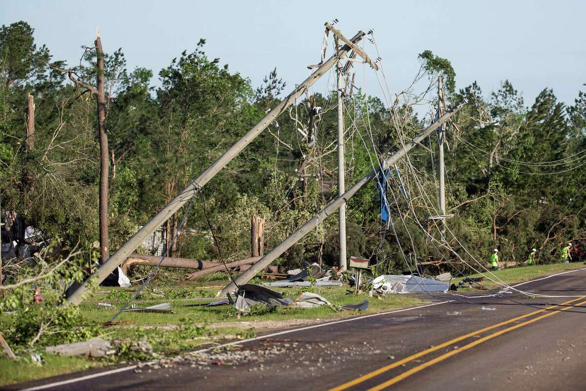 FILE - In this April 23, 2020 file photo, utility poles are knocked off their foundation, dropping power lines, after a tornado ripped a swath of destruction through the area in Onalaska, Texas. So far, 2020 has been full of reminders that disasters can strike anytime. Fortunately, you have time to prepare your financial records for easy retrieval during storm and wildfire season. Take steps to gather and make copies of your important information, including identification and medical and financial records. (Brett Coomer/Houston Chronicle via AP, File)