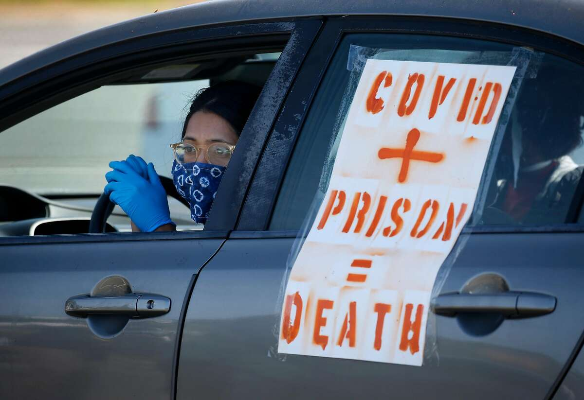 A demonstrator waits in her car before a rolling protest caravan departs for the west gate of San Quentin State Prison to demand more protection against the COVID-19 coronavirus for prisoners in Larkspur, Calif. on Saturday, May 9, 2020.