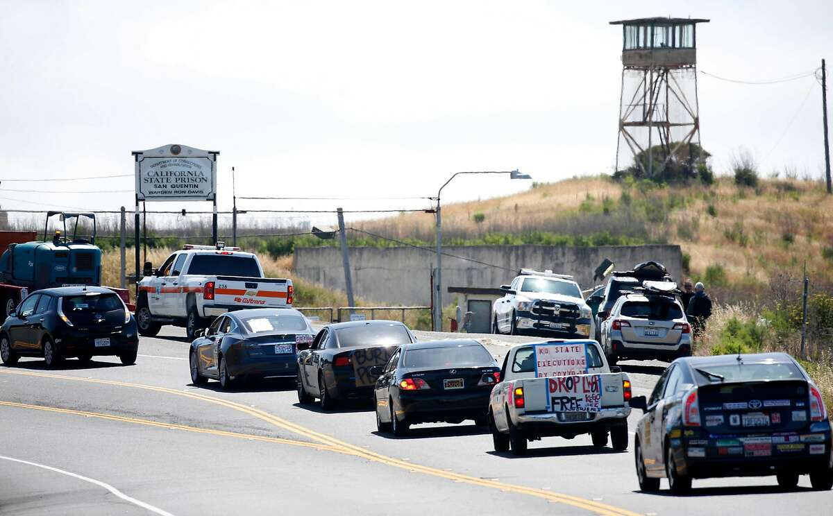 A long caravan of cars drives past the west gate of San Quentin State Prison to demand more protection against the COVID-19 coronavirus for prisoners in Larkspur, Calif. on Saturday, May 9, 2020.