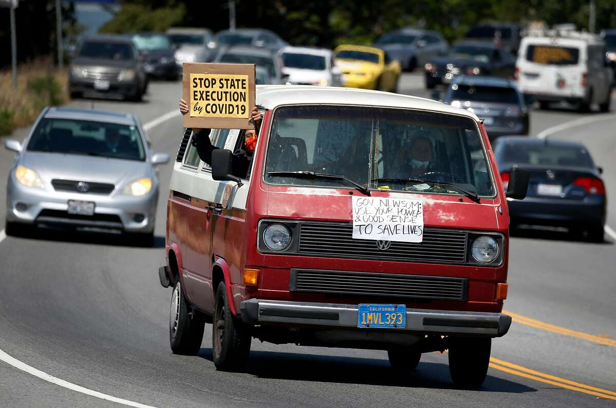 A long caravan of cars drives toward the west gate of San Quentin State Prison to demand more protection against the COVID-19 coronavirus for prisoners in Larkspur, Calif. on Saturday, May 9, 2020.