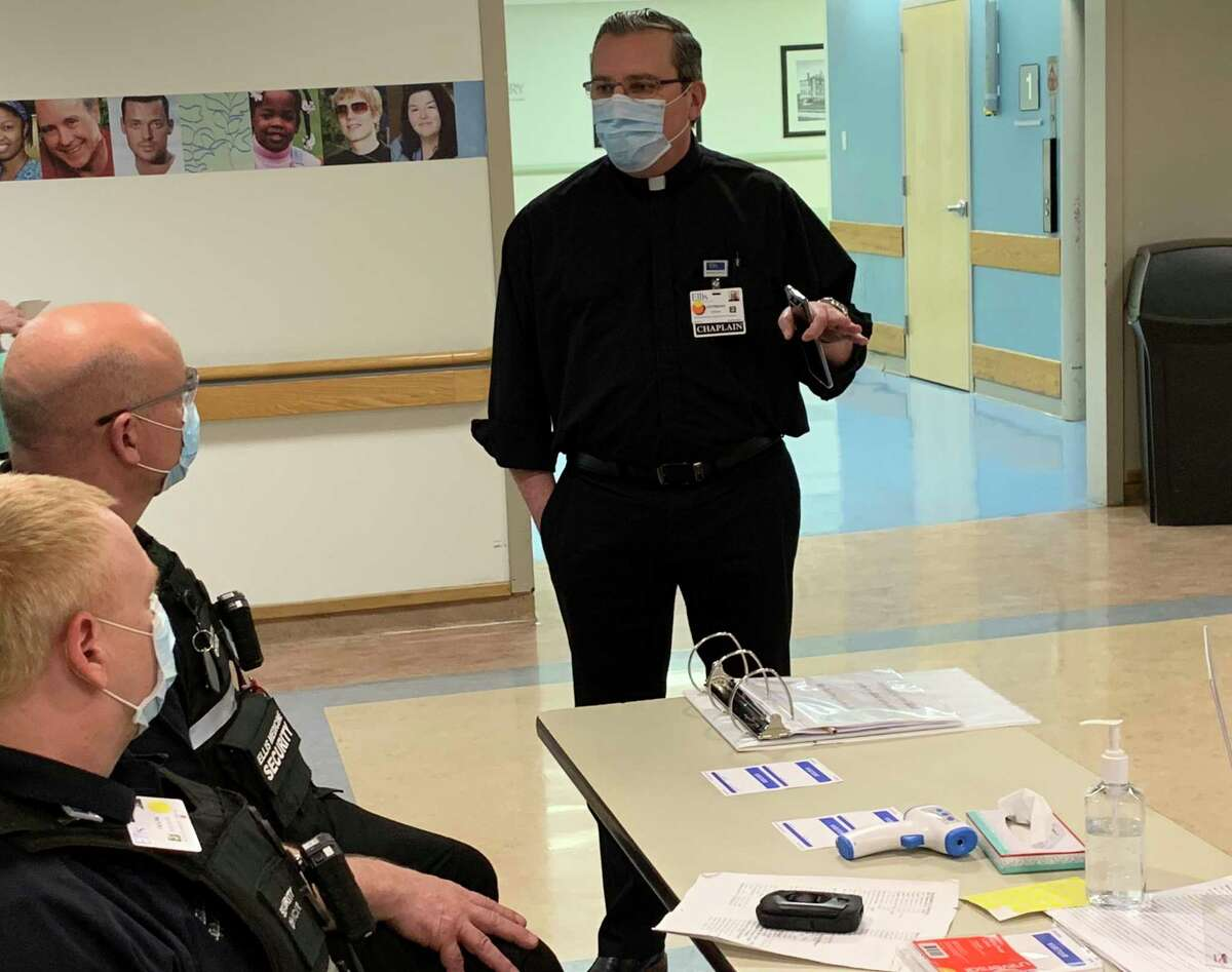 Father Tony Green, Director of Pastoral Care and Volunteer Services at Ellis Hospital, on the job talking to members of Ellis Hospital Security.