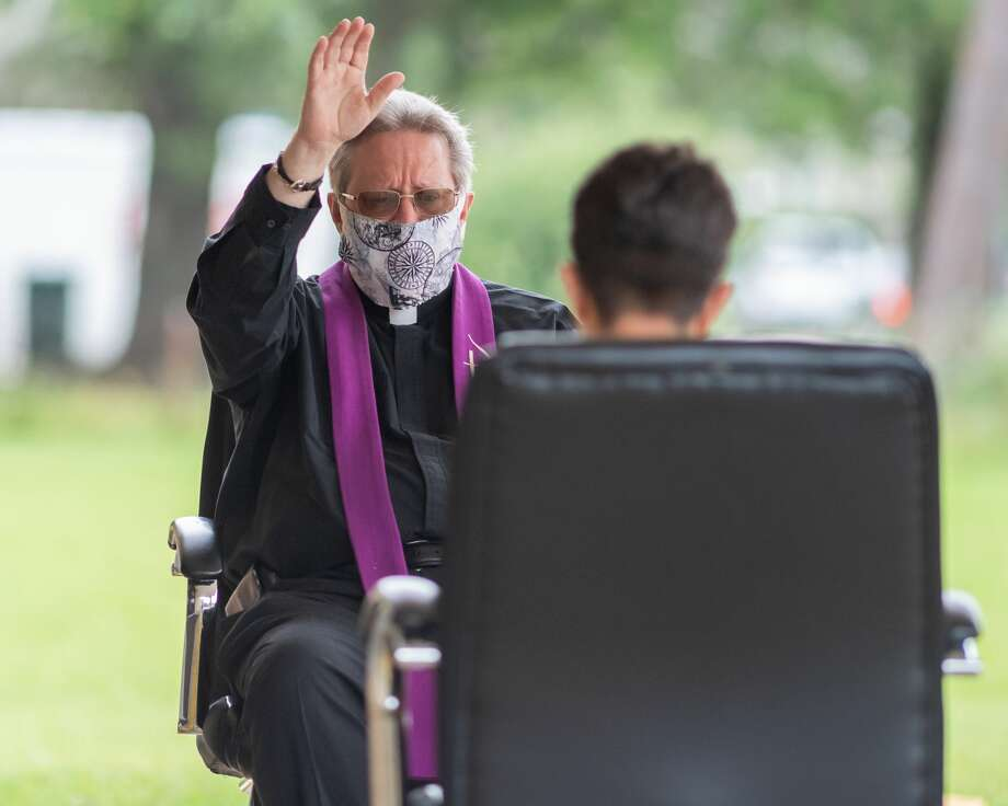 Wearing a mask and keeping the six feet social distance, Father Kevin Badeaux hears a young parishioner's confession outside the Cody Center of St. Joseph Catholic Church in Port Arthur on Saturday afternoon. The parish has been providing outdoor confession for the past several weeks and will be distributing Communion to parishioners in the parking lot on Sunday afternoon. Photo made on May 9, 2020. Fran Ruchalski/The Enterprise Photo: Fran Ruchalski/The Enterprise / ? 2020 The Beaumont Enterprise
