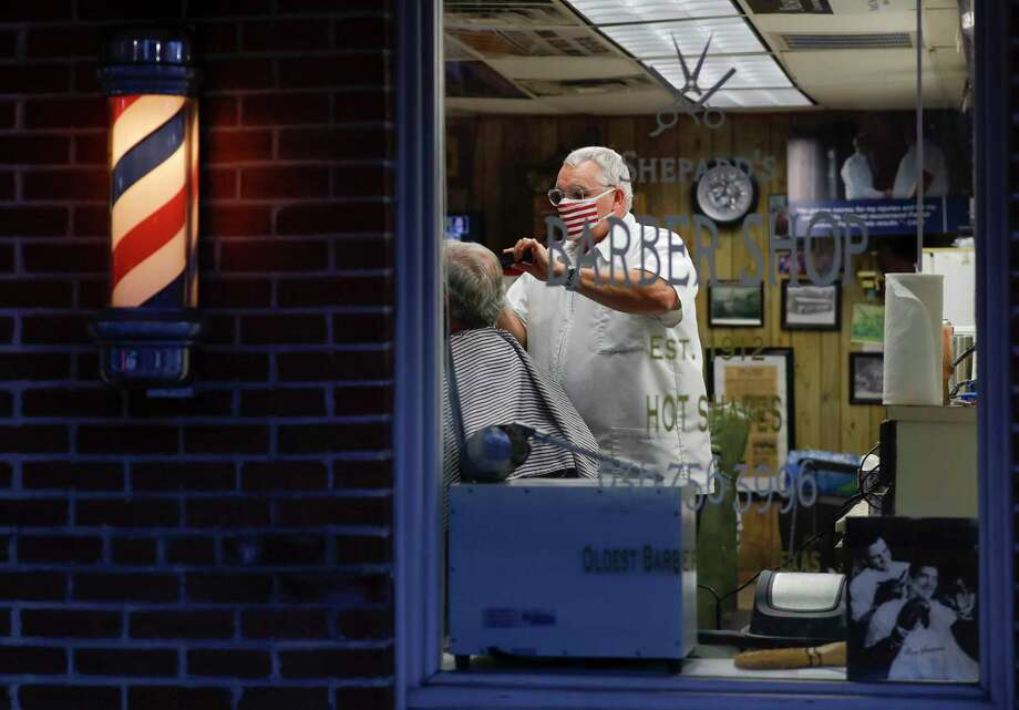 Owner Leon Apostolo cuts the hair of Larry Forester as he takes in customers well into the late evening at Shepard's Barber Shop, Friday, May 8, 2020, in Conroe. Apostolo started his day at 5:00 a.m. and said he already had three customers waiting for him. One man had been waiting since 4:30 a.m. Gov. Greg Abbott modified initial executive order to reopen the Texas economy on Tuesday to allow barbershops, nail salons and hairdressers to reopen Friday with some social distancing and hygiene protocols. Photo: Jason Fochtman, Houston Chronicle / Staff Photographer / 2020 © Houston Chronicle
