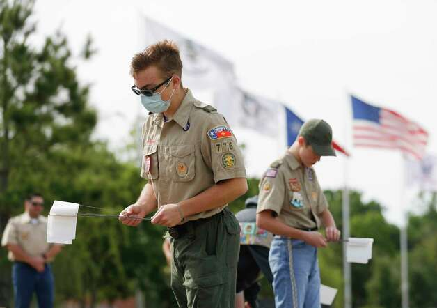 Boy Scout James Custer with Troop 776 helps place small flags at the Montgomery County Veterans Memorial Park, Saturday, May 9, 2020, in Conroe. Volunteers planted more than 1,000, red, white, and blue flags representing those who have died from COVID-19 from Texas so far. Photo: Jason Fochtman, Staff Photographer / 2020 © Houston Chronicle