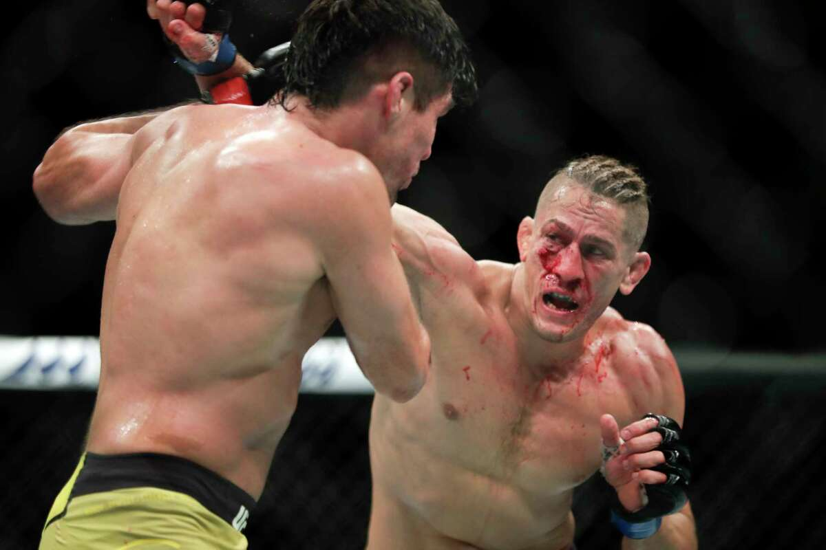 Niko Price, right, throws a punch to Vicente Luque during a UFC 249 mixed martial arts bout, Saturday, May 9, 2020, in Jacksonville, Fla. (AP Photo/John Raoux)