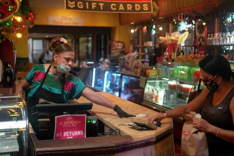 """Luz Arrendondo, 50, helps customer Michelle Hanson visiting from Kansas City at Mi Tierra Cafe y Panaderia in San Antonio, Texas on May 8, 2020. Arrendondo is known as """"La Mama de Bakery,"""" a title she earned after years of working holidays, weekends and long hours at the cafe she calls her American dream."""