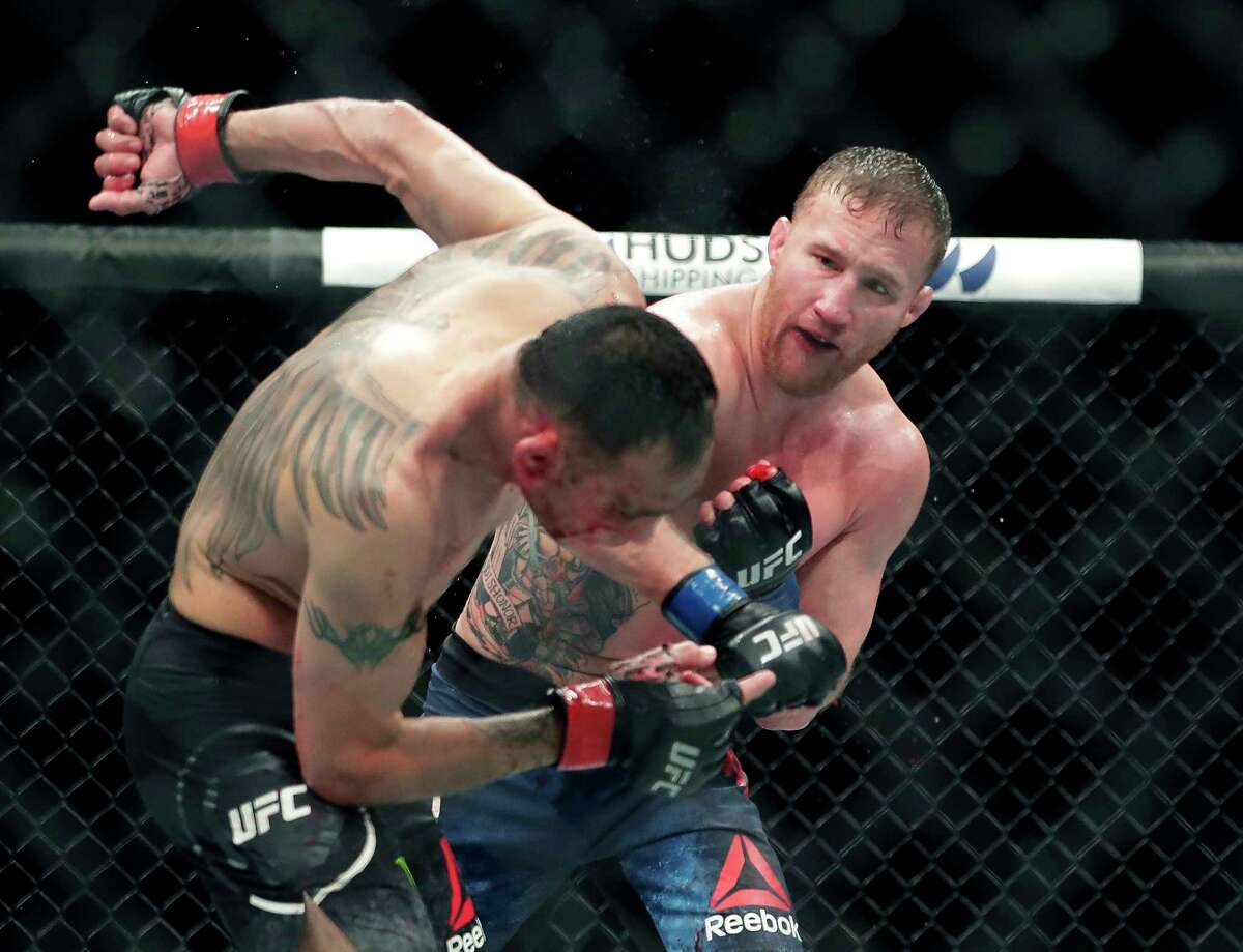 Tony Ferguson, left, falls backward after taking a punch from Justin Gaethje during a UFC 249 mixed martial arts bout, early Sunday, May 10, 2020, in Jacksonville, Fla.