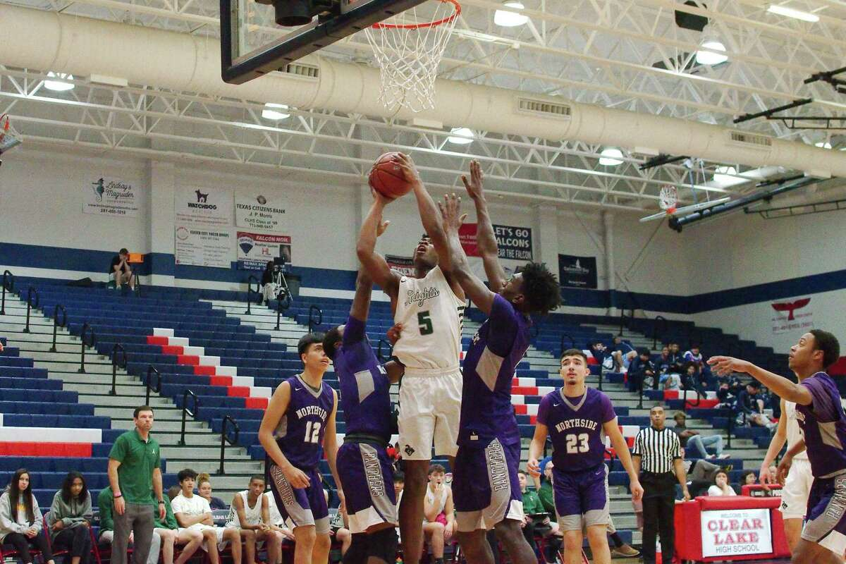 Clear Falls' Corey Kelly (5) puts up a shot over Northside's Ronald Holmes (5) and Jeremiah Richardson (1) Thursday, Dec. 5 during the Carlisle-Krueger Classic basketball tournament at Clear Lake High School.