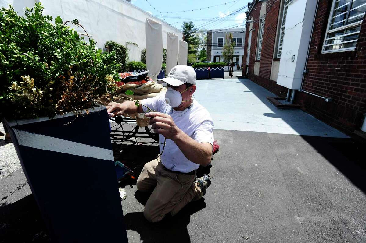 A contractor paints flower pots at Le Fat Poodle restaurant on May 7, 2020. Le Fat Poodle plans to re-open sit-down dining on May 20, 2020, when restaurants in Connecticut are allowed to do outdoor seating.