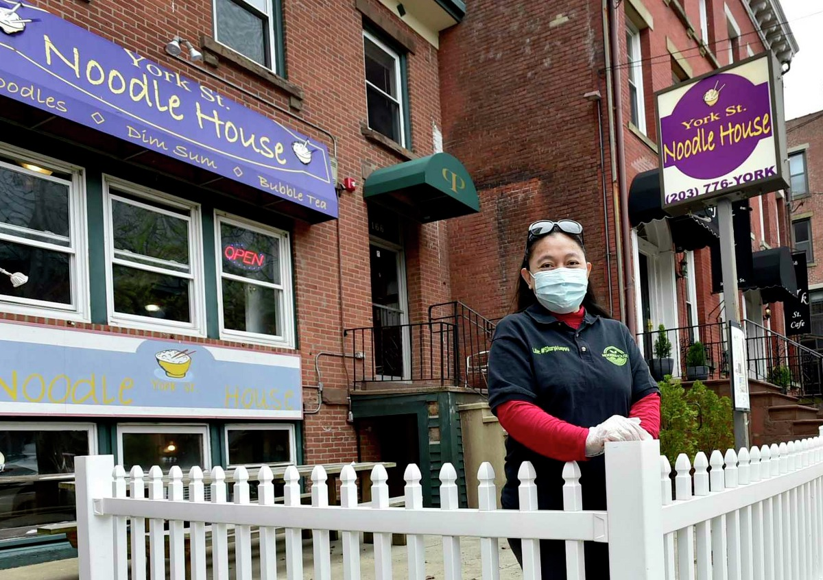 Soraya Kaoroptham stands in the outdoor seating area of the York St. Noodle House that she owns in New Haven, Conn.