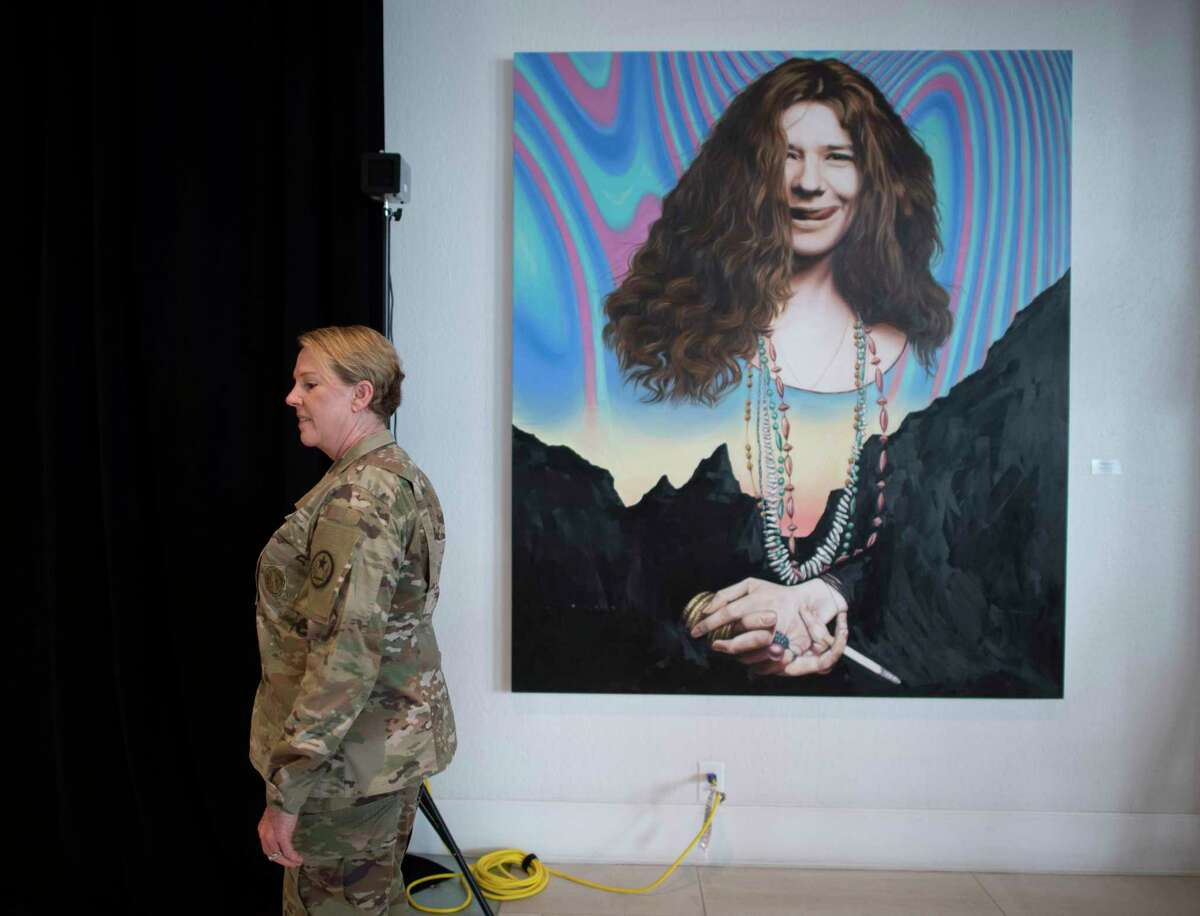 Texas National Guard Maj. Gen. Tracy Norris has her temperature checked as she stands by a portrait of the musician Janis Joplin in Austin on Friday.The guard has soldiers and airmen supporting coronavirus response missions around the state.