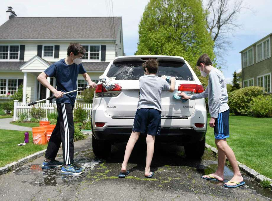 Patrick Sullivan, left, 16, washes a neighbor's car with his brothers Cole, right, 14, and Luke, 10, in Old Greenwich on Sunday. The Sullivan brothers are raising money washing cars to donate to the Greenwich nonprofit food pantry Neighbor-to-Neighbor. The GoFundMe has raised $1,400 as of Sunday. Photo: Tyler Sizemore / Hearst Connecticut Media / Greenwich Time
