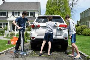 Patrick Sullivan, left, 16, washes a neighbor's car with his brothers Cole, right, 14, and Luke, 10, in Old Greenwich on Sunday. The Sullivan brothers are raising money washing cars to donate to the Greenwich nonprofit food pantry Neighbor-to-Neighbor. The GoFundMe has raised $1,400 as of Sunday.