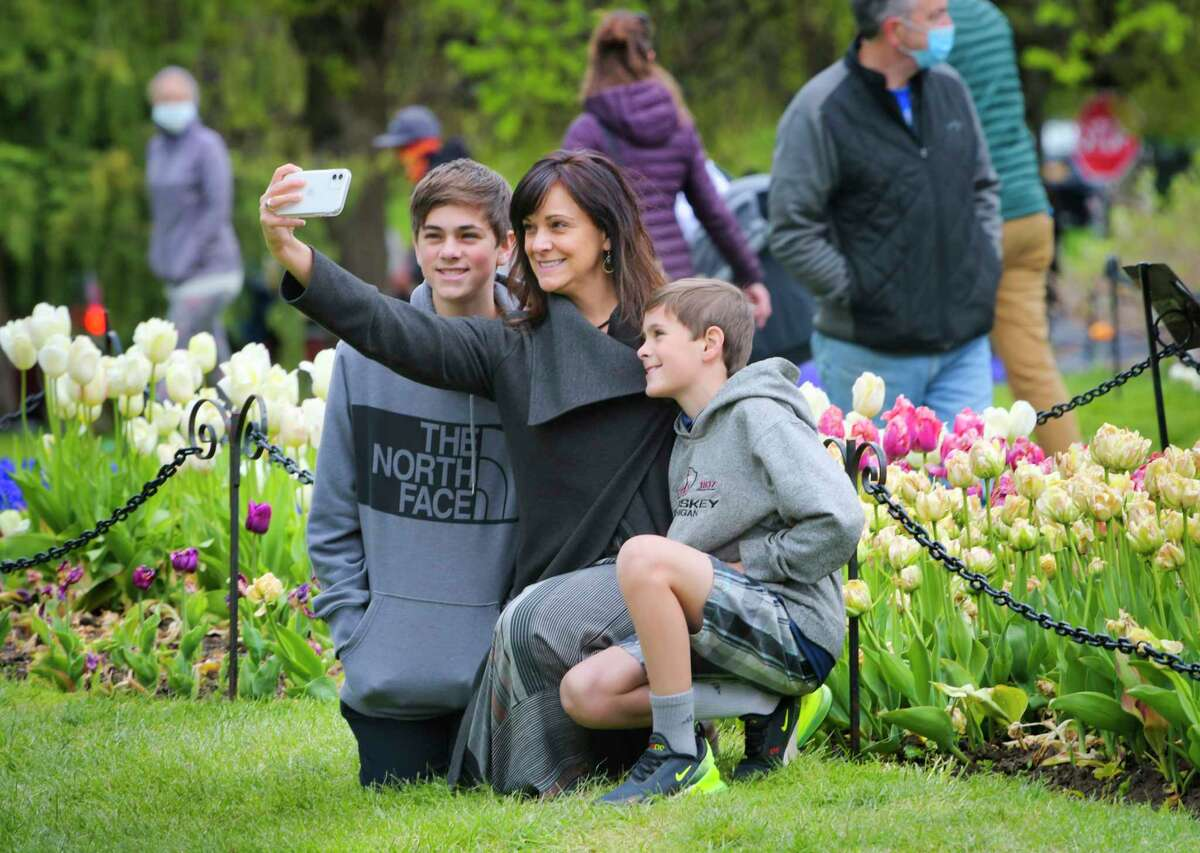 Dawn DiLorenzo of Charlton takes a photo with her sons, Ben, left, 14, and Jack, 11, at Washington Park on Sunday, May 10, 2020, in Albany, N.Y. This past weekend would have been the Albany Tulip Festival at the park but the event was canceled due to the pandemic. (Paul Buckowski/Times Union)