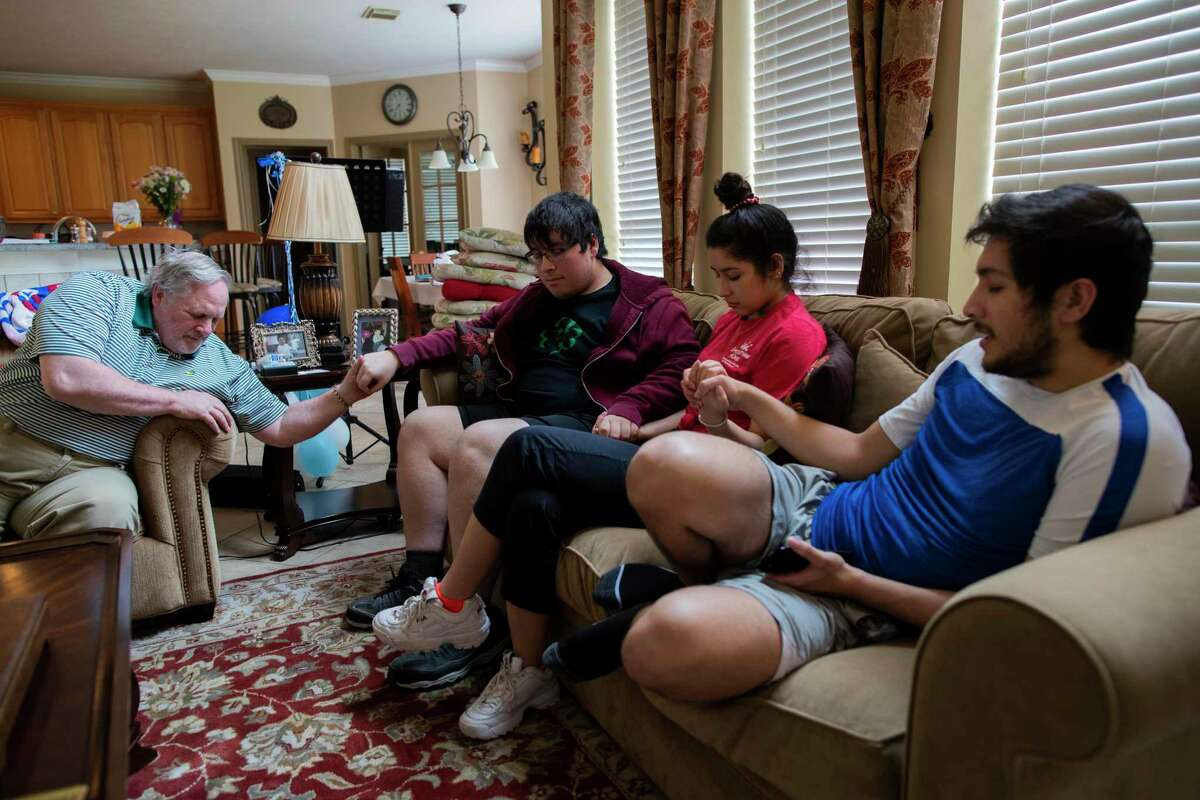 Daniel Topp, 63, and his adult children Nickolas Topp, 19, Hannah Topp, 18, and Leonard David Topp, 22, hold hands in prayer on Saturday, May 9, 2020, in Kingwood after talking as a family about the things they wish to do together to strengthen their bond while Daniel's wife Eleana Topp continues in the hospital battling COVID-19.