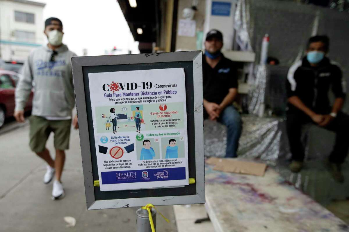 Guidelines on how to avoid the spread of COVID-19 are displayed on Mother's Day at the Los Angeles Flower Market, Sunday, May 10, 2020, in Los Angeles. Families in the U.S. and elsewhere marked Mother's Day in a time of social distancing and isolation due to the coronavirus pandemic.