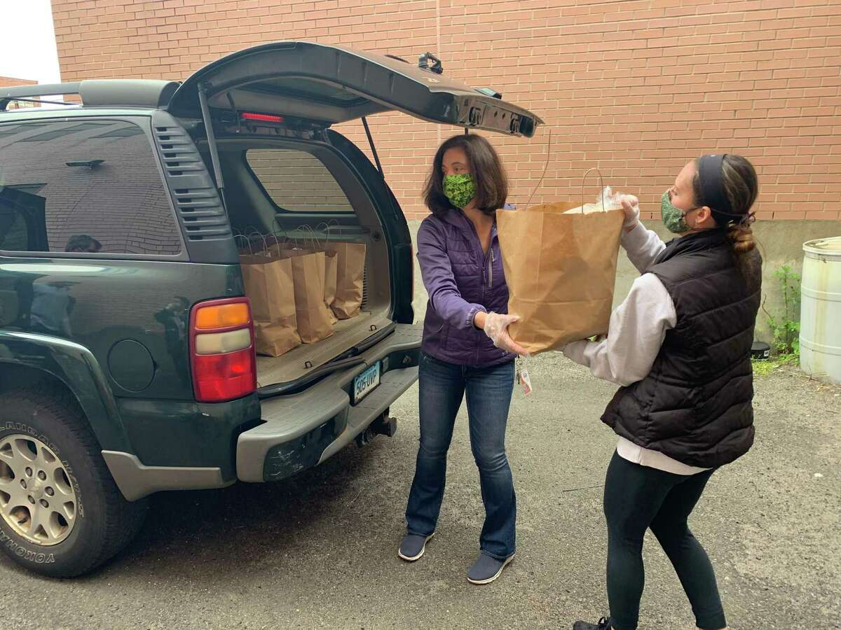 Hannah Lillicraf of Trumbull, a Hall Neighborhood House volunteer hands a bag of food that Cheryl Delaney loads into Terri Williams's SUV so it could be delivered to a Bridgeport senior citizen.