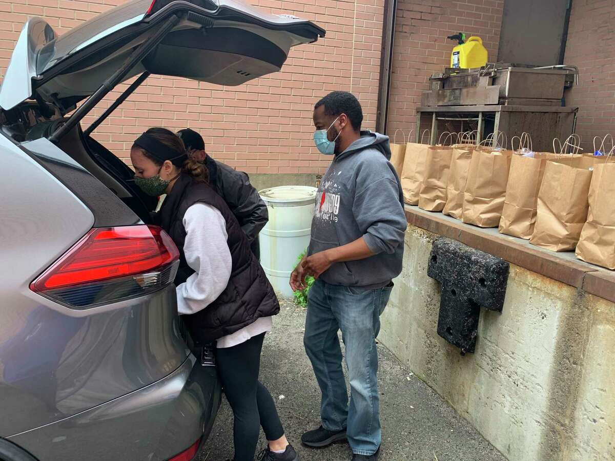Hannah Lillicraf, a Hall Neighborhood House volunteer, loads a bag of food into Sean McBride's SUV as he prepares to make deliveries to senior citizens in Bridgeport.
