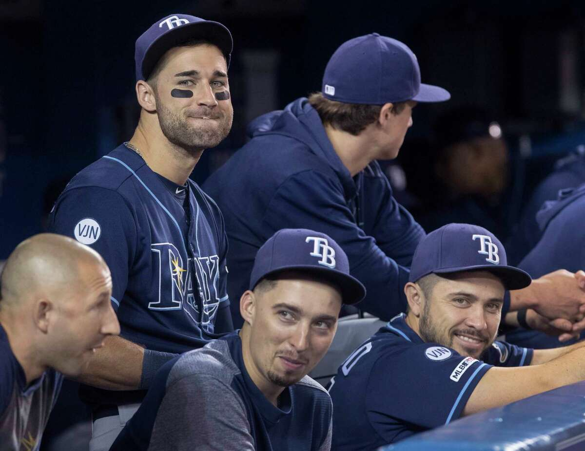 FILE - In this Sept. 28, 2019, file photo, Tampa Bay Rays' Kevin Kiermaier, top left, relaxes in the dugout with teammates in the fourth inning of a baseball game against the Toronto Blue Jays in Toronto. Major League Baseballa€™s average salary as opening day approached remained virtually flat at around $4.4 million for the fifth straight season, according to a study of contracts by The Associated Press. (Fred Thornhill/The Canadian Press via AP, File)