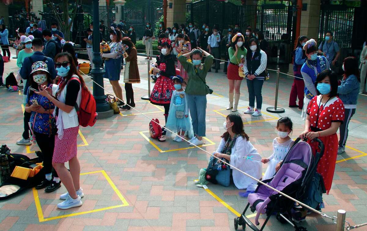 Visitors, wearing face masks, wait to enter the Disneyland theme park in Shanghai as it reopened, Monday, May 11, 2020. Visits will be limited initially and must be booked in advance, and the company said it will increase cleaning and require social distancing in lines for the various attractions. With warmer weather and new coronavirus cases and deaths falling to near-zero, China has been reopening tourist sites such as the Great Wall and the Forbidden City palace complex in Beijing.