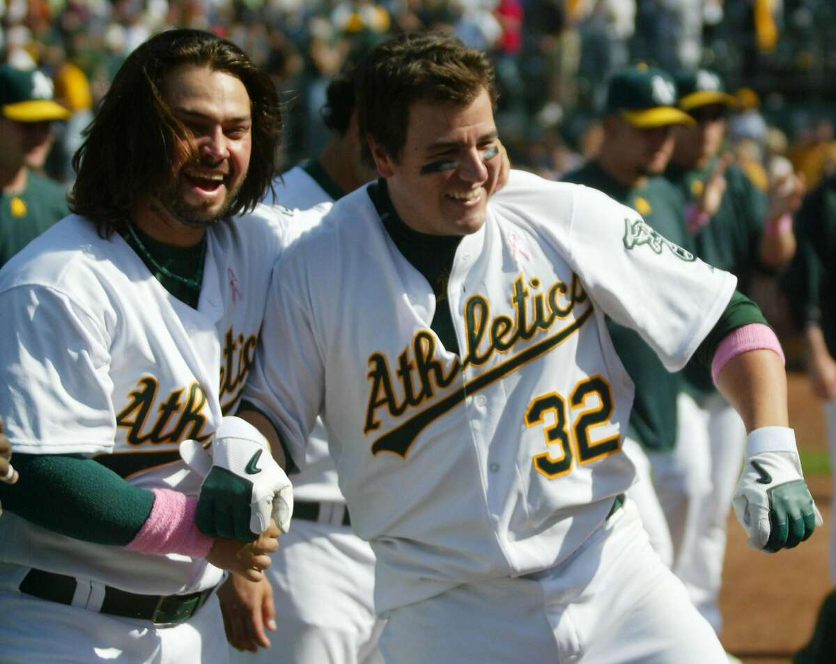 OAKLAND, CA - MAY 13: Jack Cust #32 of the Oakland Athletics is congratulated by Nick Swisher #33 after hitting a walk-off home run in the ninth inning of a Major League Baseball game against the Cleveland Indians on May 13, 2007 at McAfee Coliseum in Oakland, California. The A's defeated the Indians 10-7. (Photo by Sara Wolfram/Getty Images)