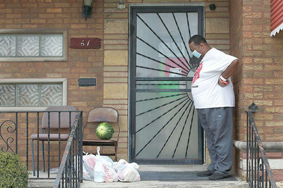 Anthony Travis, who has recovered from COVID-19 and lives with his sister and an adult daughter, looks at a surprise anonymous delivery of groceries on the porch of his Riverdale home. Photo: Charles Rex Arbogast | AP