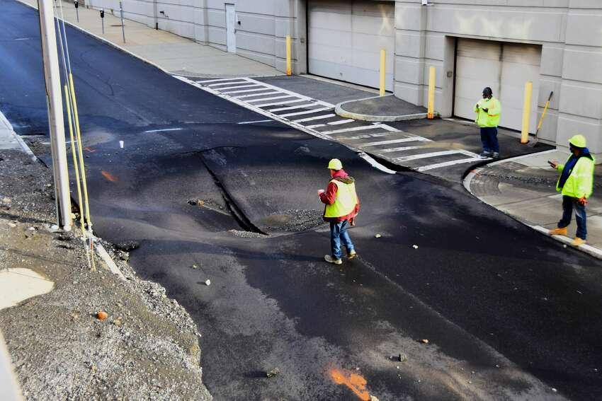 City workers inspect a sinkhole on Orange Street in downtown Albany after what they described as a 12-inch water main broke around 4 a.m. Monday. The subsequent flood affected Orange, Chapel and Monroe streets, portions of all of which had been resurfaced and had new sidewalks installed within the past month. Water also undermined the sidewalk going into the rear garage of the Albany County Family Court building, right. Orange Street was closed between Chapel Street and Theatre Row. (Photo by Steve Barnes/Times Union)