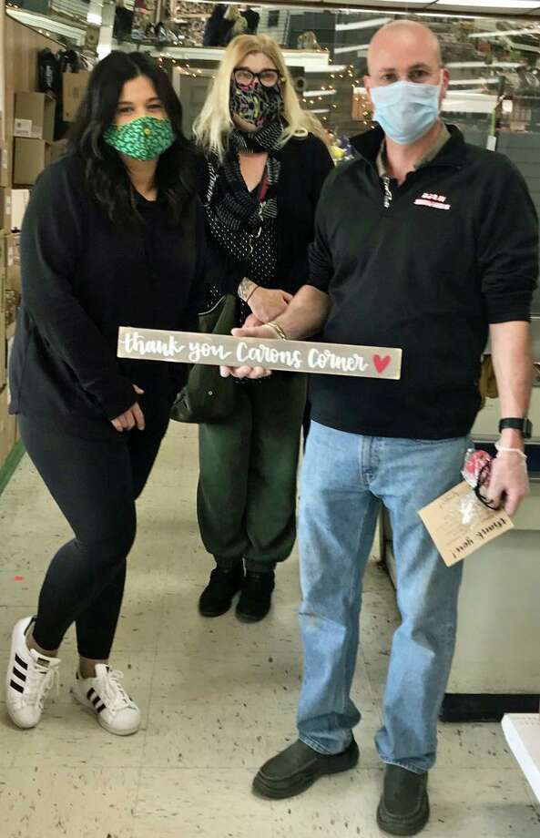 Branford's Tina Pace, left, and Cheryl Andrese, administrators of a Facebook page named for the female dog, delivering $10 Hornets Nest gift cards to Dave Caron, owner of Carons Corner, for his 30 employees, with sign made by Pace, owner of Writeboard in Branford. Photo: Contributed Photo