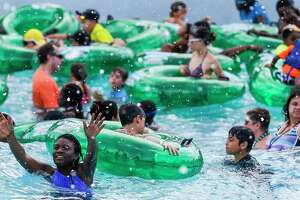 A girl reaches for fake snow falling into Tidal Wave Bay as people beat the heat at Typhoon Texas where the water park is celebrating Christmas in July on Wednesday, July 25, 2018, in Katy.