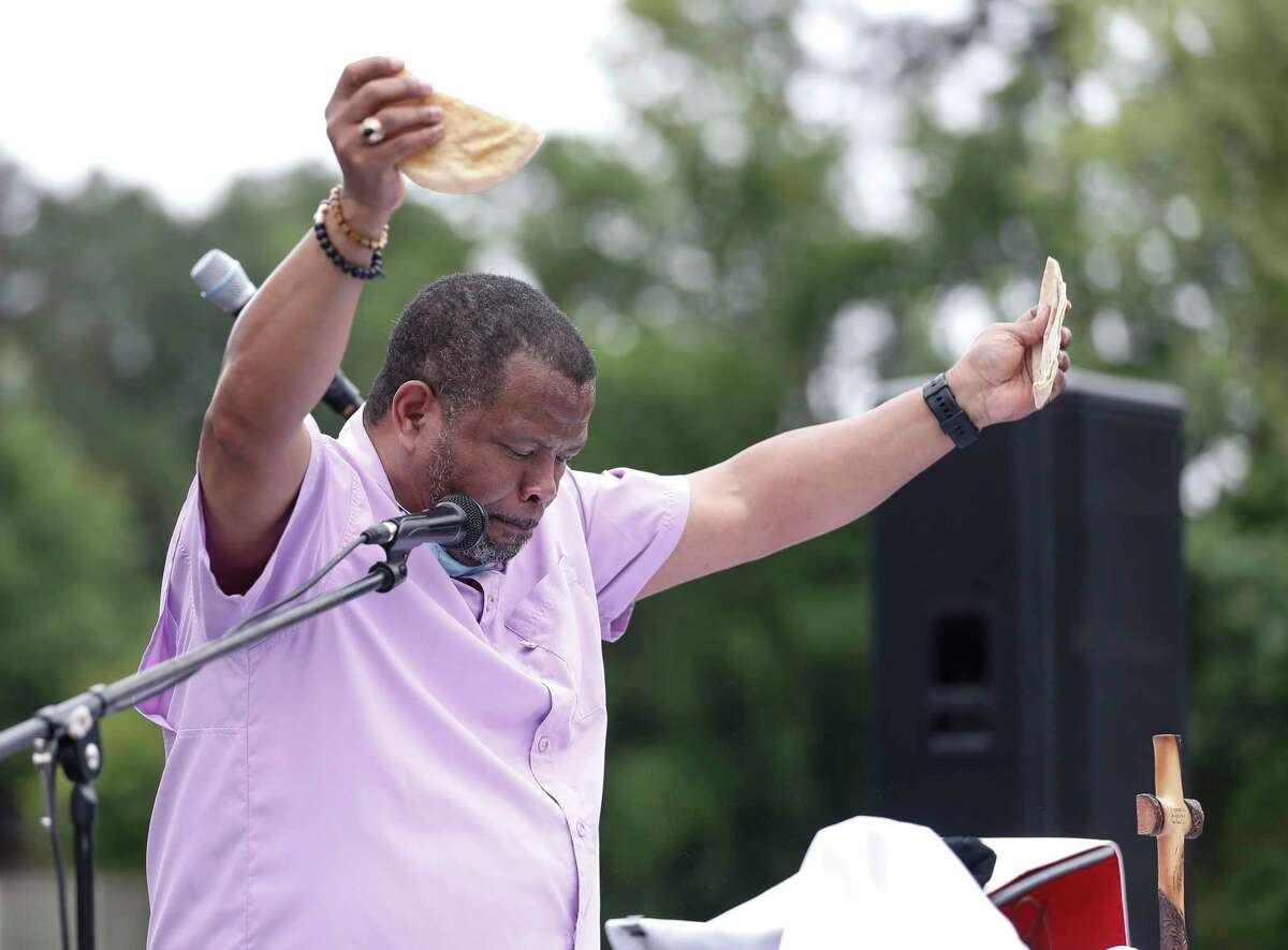 Pastor Steffon Arrington breaks the bread during Communion of his Palm Sunday services for worshippers, who sat in their cars, in the parking lot of Spring Woods United Methodist Church, in Houston,Sunday, April 5, 2020. Communion was offered during the service, but with individual, pre-packaged wafers and juice.