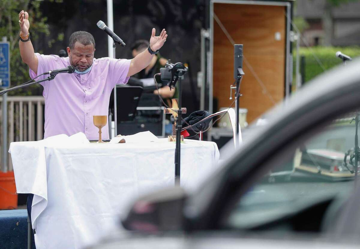 Pastor Steffon Arrington conducts Palm Sunday services to worshippers, who sat in their cars, in the parking lot of Spring Woods United Methodist Church, in Houston,Sunday, April 5, 2020. Communion was offered during the service, but with individual, pre-packaged wafers and juice.