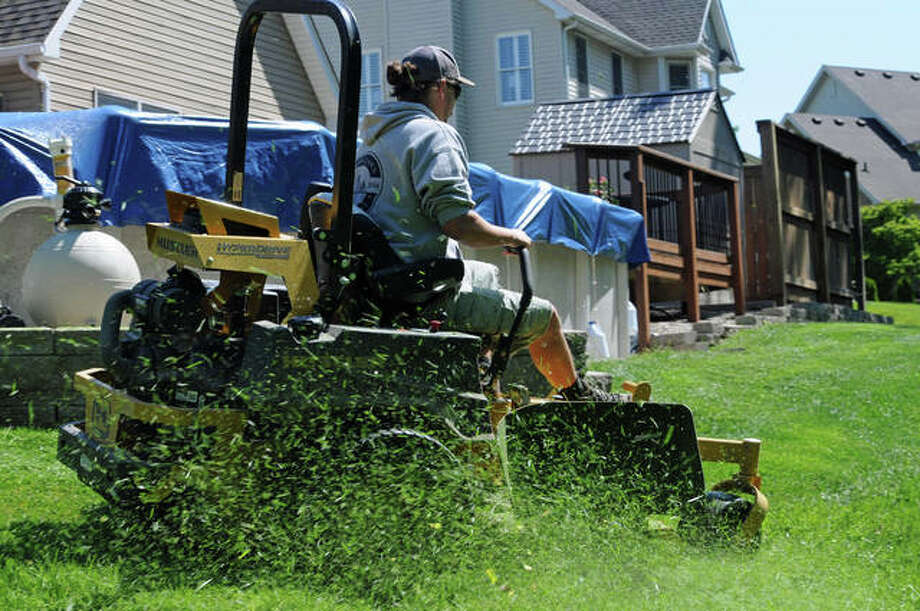 Adam Stenhaug of Alton, an employee of Alton Lawn Company, mows a residential yard in Godfrey. Tyler Dreith of the firm said keeping mower blades sharp provides a cleaner cut and reduces the work on an engine.