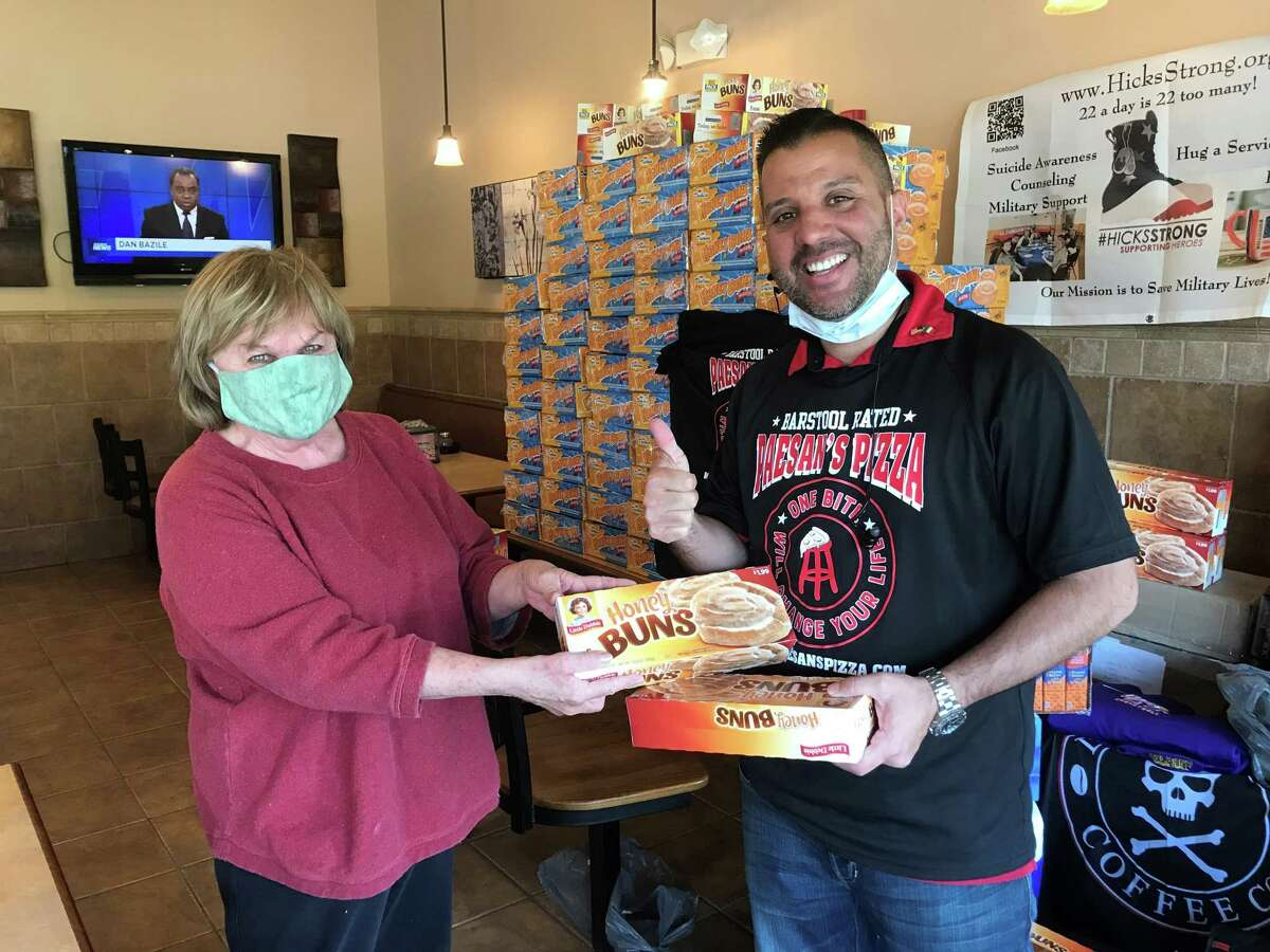 Regina Brown of Latham donates items to and Frank Scavio, Paesan's Paesan's Pizza owner, for shipment in care packages to soldiers on duty in Afghanistan. (Provided)