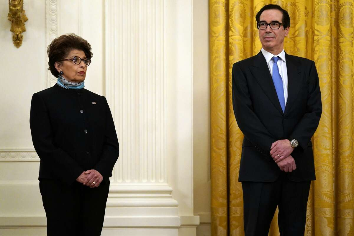 Jovita Carranza, administrator of the Small Business Administration and Treasury Secretary Steven Mnuchin listen as President Donald Trump speaks during an event about the Paycheck Protection Program used to support small businesses during the coronavirus outbreak, in the East Room of the White House, April 28, 2020, in Washington. (AP Photo/Evan Vucci)