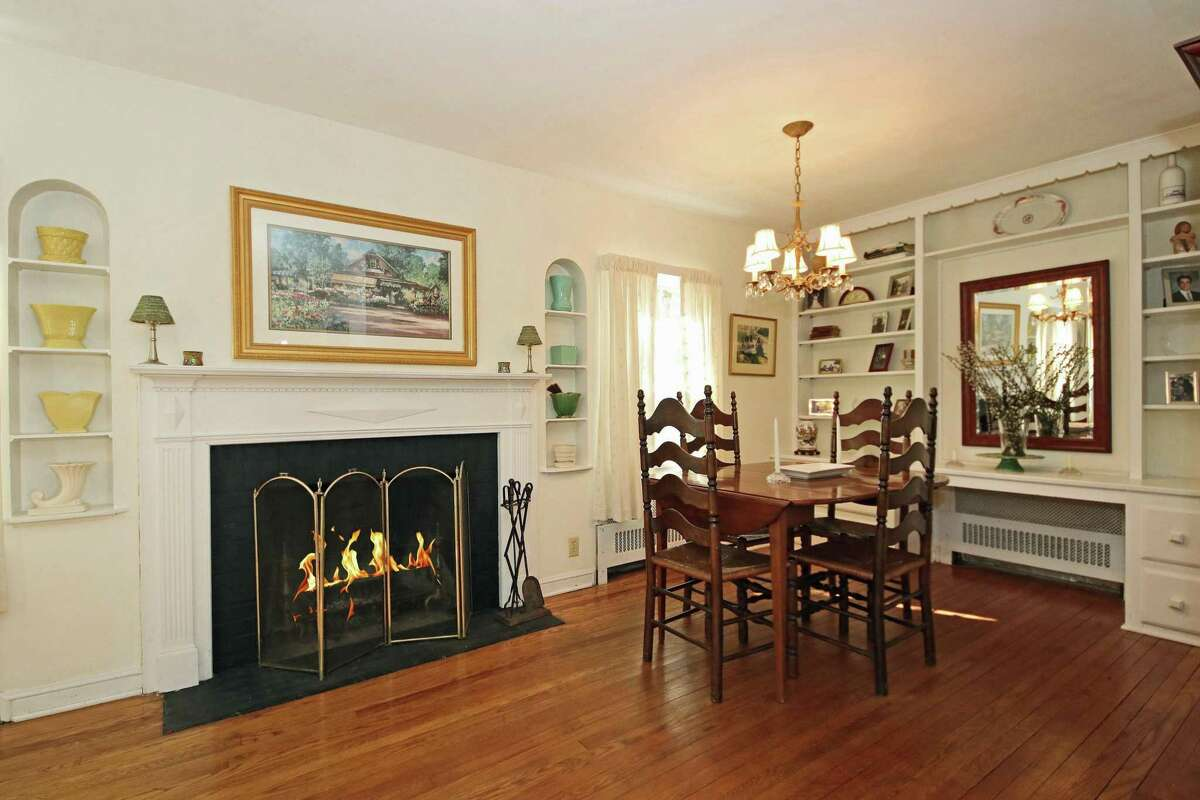 Between the living and dining rooms there is a wood-burning fireplace with a decorative mantel flanked by recessed display shelves.