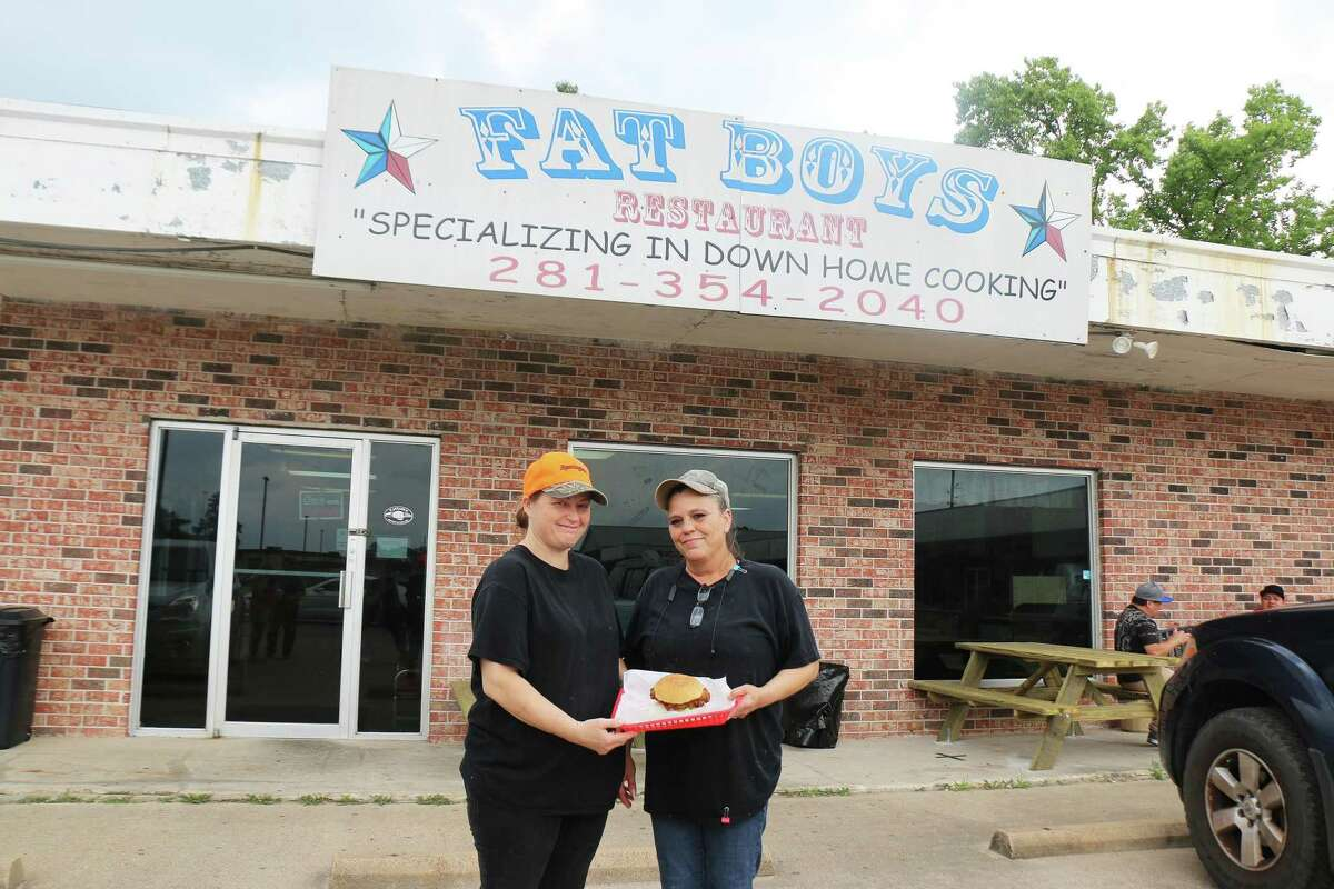 Wendy Cisco and Wanda Holland hold one of the restaurant favorites, a chicken-fried steak sandwich. The business reopened for customers at 25 percent occupancy and had a steady crowd the first day.