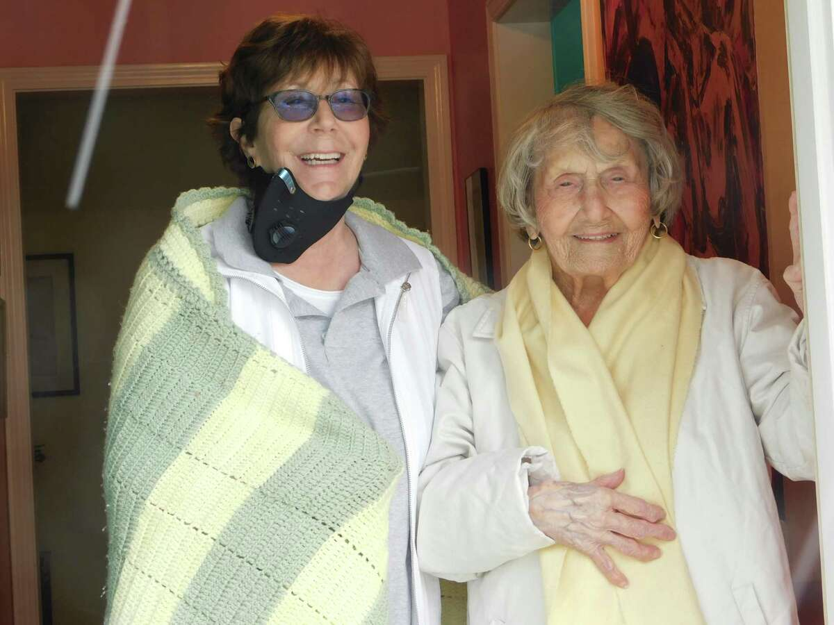 Nutmeg Conservatory founder Sharon Dante, left, and her mother, Marjorie Dante, who turned 100 on Friday, greet well-wishers from their doorway on Friday. Friends and members of the conservatory marked the elder Dante's special day with an outdoor gathering.