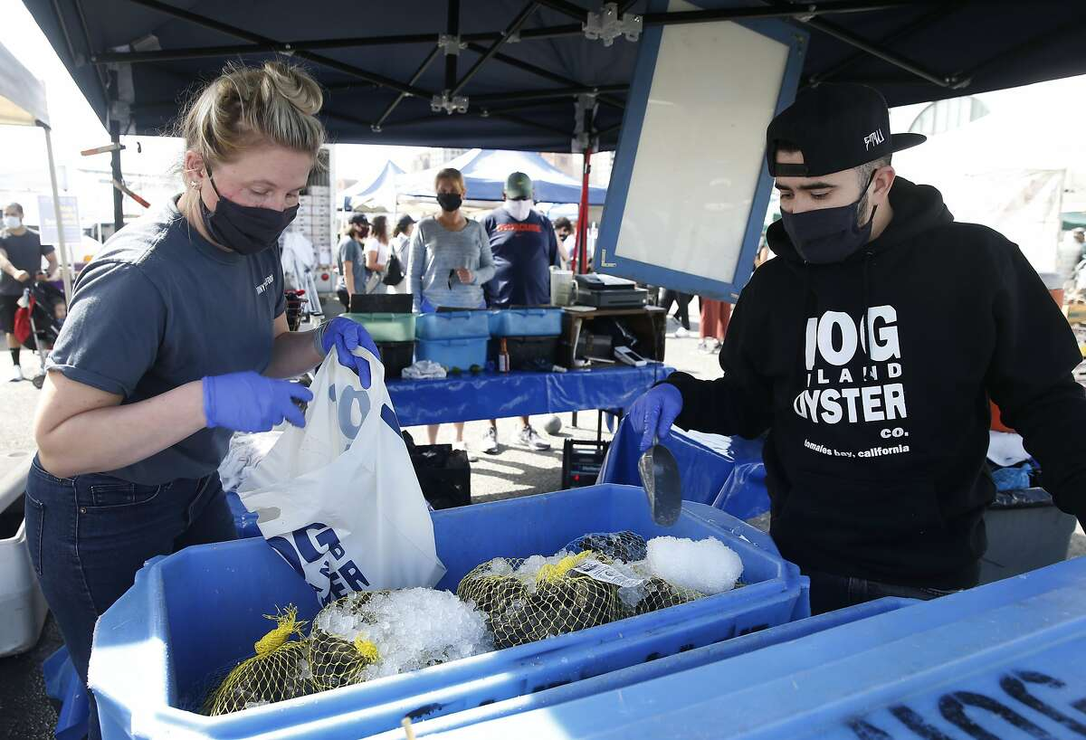 Andi Suhr (left) and Brayan Flores fills a bag with oysters for customers at the Hog Island Oyster Company stand at the Ferry Plaza Farmers' Market in San Francisco, Calif. on Saturday, April 25, 2020. The shellfish industry has been hit hard by the coronavirus pandemic as shelter in place orders have forced restaurants to shutdown.
