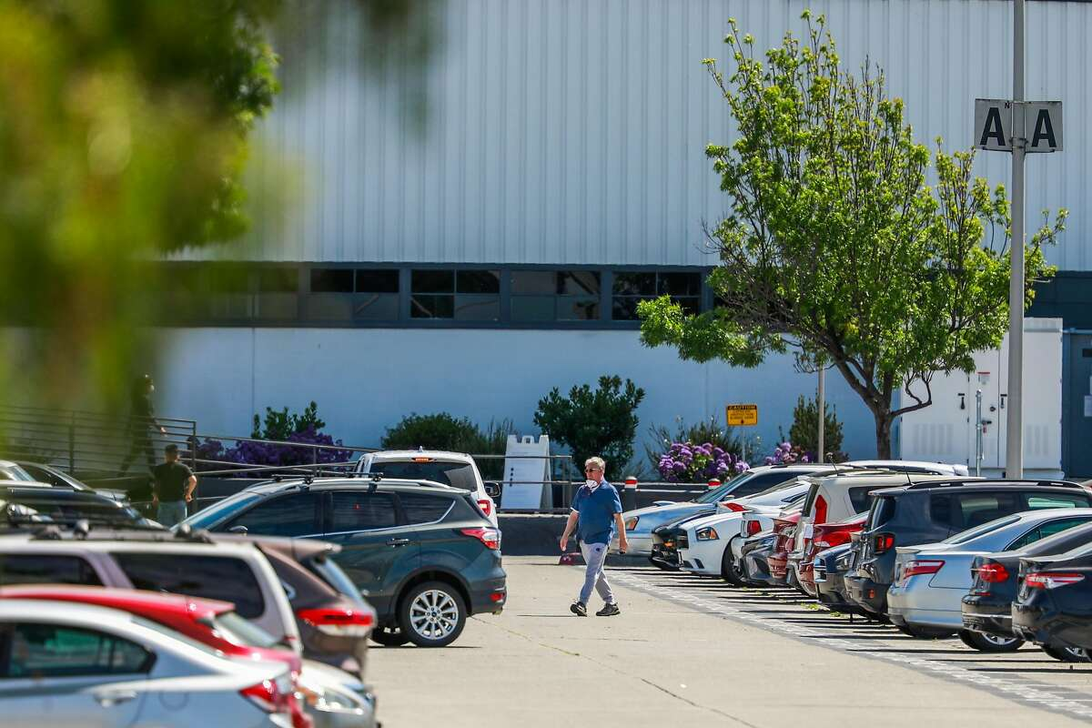 A man walks through the parking lot at the Tesla car factory on Monday, May 11, 2020 in Fremont, California. Tesla has reopened its Fremont car factory in defiance of county rules prohibiting car manufacturing during shelter-in-place.