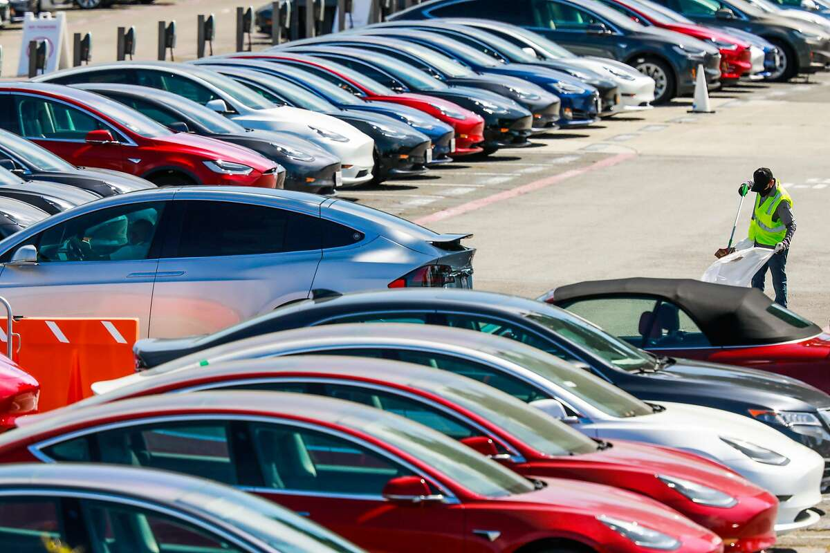A man cleans the parking lot at the Tesla car factory on Monday, May 11, 2020 in Fremont, California. Tesla has reopened its Fremont car factory in defiance of county rules prohibiting car manufacturing during shelter-in-place.